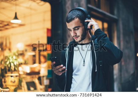 Handsome young guy walking outdoors using mobile phone listening music. Stock photo © deandrobot