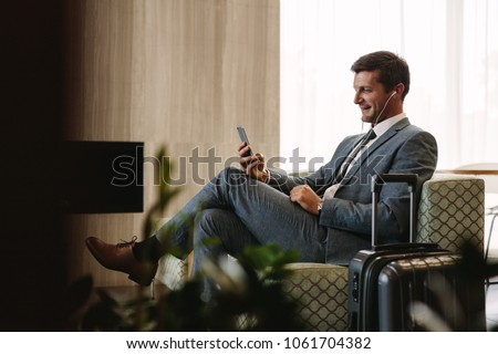 Stock photo: A man in the lounge area at the airport is waiting for his plane, uses a smartphone and headphones.