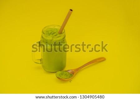 Green tea latte with ice in mason jar and straw and spoon with powder matcha on yellow background. H Сток-фото © galitskaya