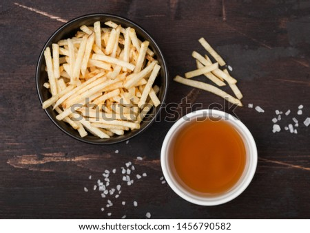 Salt and vinegar potato sticks in white bowl, classic snack with ketchup on wooden background.  Stock photo © DenisMArt