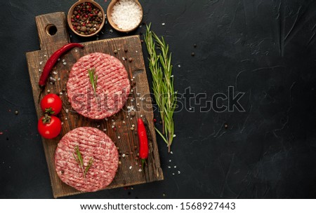Stock photo: Fresh grilled and raw minced pepper beef burger on stone chopping board with buns onion and tomatoes