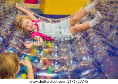 Cute little boy and girl playing in Zorb a rolling plastic cylinder ring with a hole in the middle,  Stock photo © galitskaya