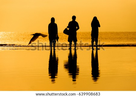 Family of three person is standing on sunset and sea backdrop Stock photo © Lopolo