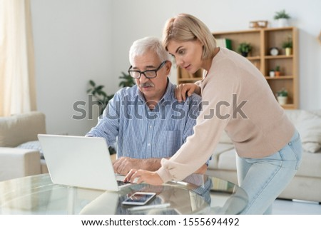 Young woman in casualwear and her senior father looking at laptop display Stock photo © pressmaster
