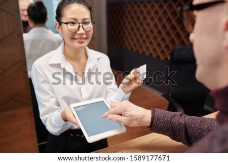 Hand of mature businessman over tablet display and young receptionist with card Stock photo © pressmaster