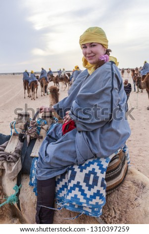 A woman dressed in a long dress sits in the desert on the cracked ground Stock photo © ElenaBatkova