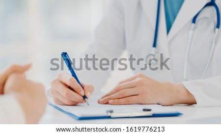 Unrecognizable woman doctor writes down in clipboard, makes prescription for patient, records data f Stock photo © vkstudio