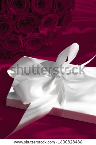Luxury holiday silk gift box and bouquet of roses on wine backgr Stock photo © Anneleven