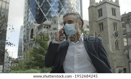 COVID-19 mask wearing business people walking in London city. Asian woman using face cover for publi Stock photo © Maridav