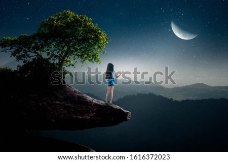 silhouette of a sad lone woman with a full moon on a cliff edge Stock photo © morrbyte