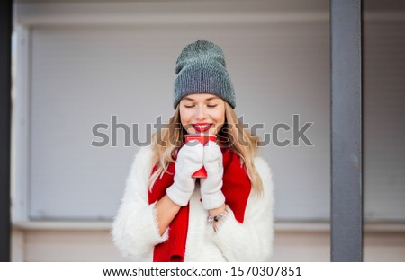 Beautiful woman in grey hat and mittens drinking hot chocolate  Stock photo © deandrobot