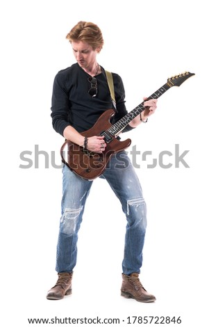 serious young male guitarist standing and playing electric guitar stock photo © deandrobot