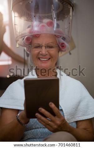 Senior woman using digital tablet while sitting under hair steamer Stock photo © wavebreak_media