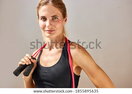 pleased sports woman posing with jumping rope and looking away stock photo © deandrobot
