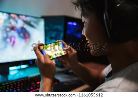 Photo of joyous gamer boy playing video games on mobile phone an Stock photo © deandrobot