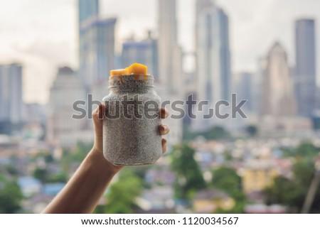 Young woman eating chia pudding on her balcony overlooking the big city Stock photo © galitskaya