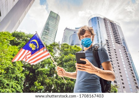 Travel and technology. Young man tourist with the flag of Malaysia is looking at a city map in a sma Stock photo © galitskaya