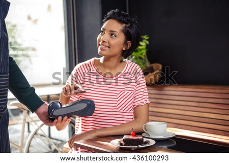 Young woman using her mobile phone for contactless payment while visiting cafe Stock photo © pressmaster