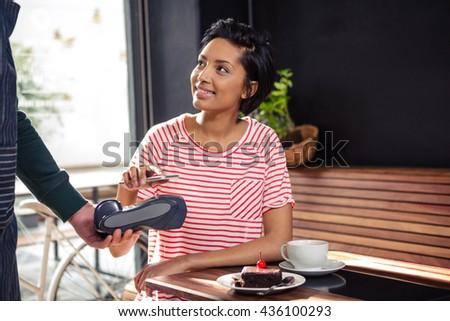 Mulher jovem telefone móvel pagamento café eletrônico Foto stock © pressmaster