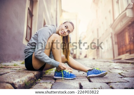 Young female runner sitting on tiled pavement in old city center Stock photo © Lopolo