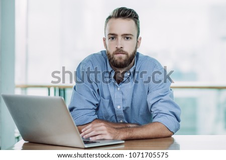 Front view of thoughtful young Caucasian businessman with mobile phone looking away in lobby office  Stock photo © wavebreak_media