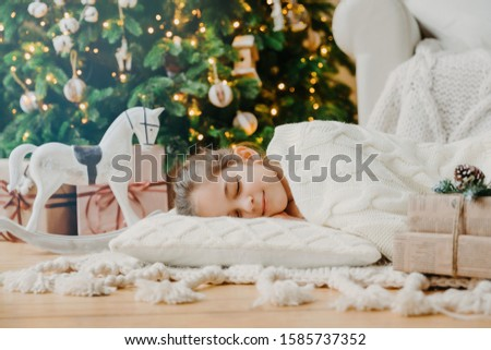 Charming girl sleeps on soft white pillow on floor against decorated New Year tree, has pleasant dre Stock photo © vkstudio