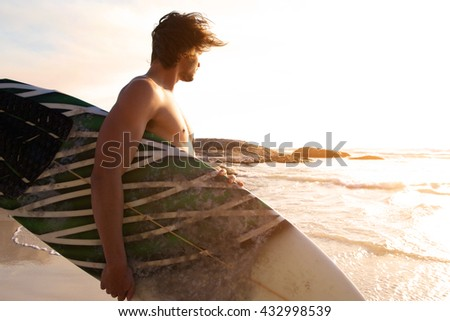 Portrait of handsome young Caucasian male surfer holding surfboard on the beach. He is looking at ca Stock photo © wavebreak_media