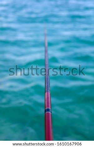 Perspective view at a fishing rod jigging for fish on of a beaut Stock photo © boggy