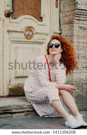 Red haired thoughtful woman has rest after strolling, poses near old building, sits on threshold, we Stock photo © vkstudio
