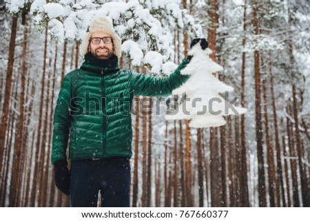 Good looking unshaven male in eyewear, wears warm winter clothes, holds white fir tree, has good moo Stock photo © vkstudio