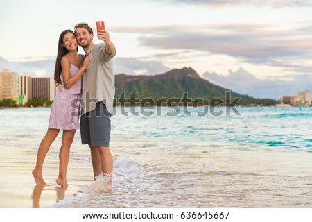 Couple walking on beach at sunset taking selfie picture on mobile phone relaxing together on Waikiki Stock photo © Maridav