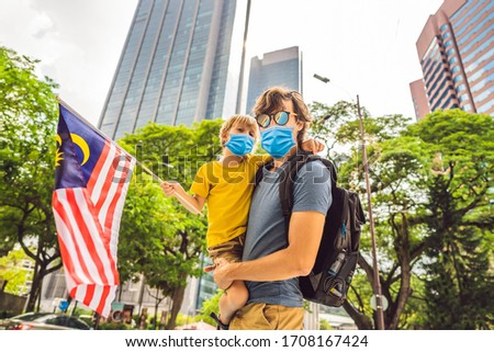 Dad and son in medical mask tourists in Malaysia with the flag of Malaysia near the skyscrapers. Tra Stock photo © galitskaya