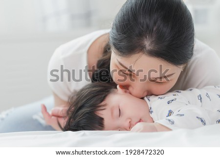 Stock photo: Portrait of an adorable mother kissing her baby in the kitchen