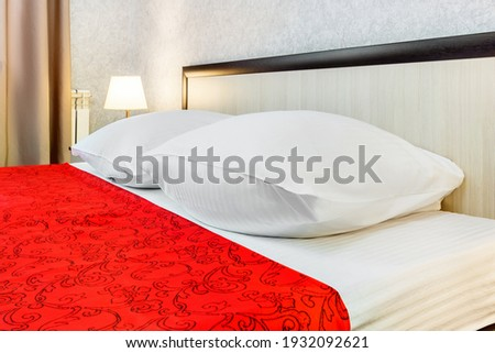 Red pillow on double bedroom with white bedsheet and lamp light  Stock photo © FrameAngel