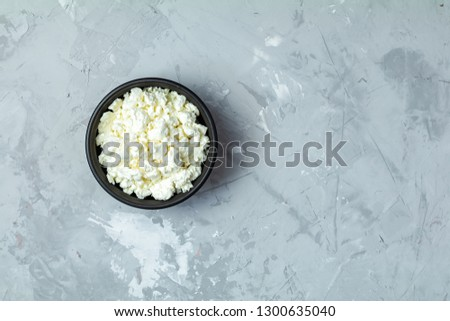 Homemade cottage cheese in a black ceramic bowl on light gray co Stock photo © artsvitlyna