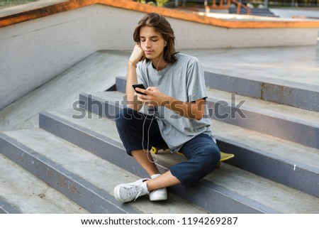 attractive oung skater guy sit in the park listening music with earphones using phone stock photo © deandrobot