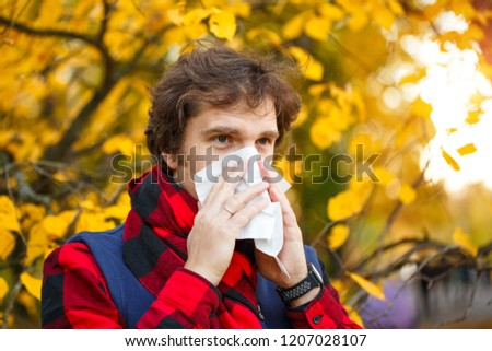 young man sneeze in the park against the background of a flowering tree allergy to pollen concept stock photo © galitskaya