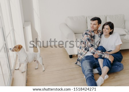 Pleased satisfied romantic couple embrace and looks out of window, pose in empty room near sofa, the Stock photo © vkstudio