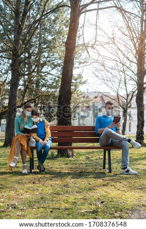 People sitting on park bench in the sun practicing social distancing Stock photo © Kzenon