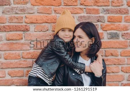 Lovely small child with pleasant appearance embraces her mother, expresses love and good feeling or  Stock photo © vkstudio