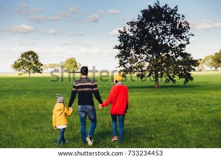 Three friendly family members have walk together on green meadow Stock photo © vkstudio