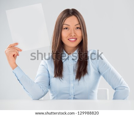 Portrait of business woman with blank sheet over gray background Stock photo © HASLOO