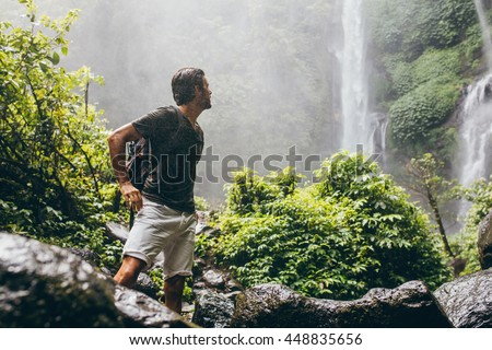 Man with backpack standing near waterfall at mountains in winter Stock photo © deandrobot