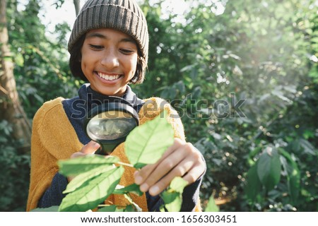 Asian little girl exploring nature with magnifier glass at outdo Stock photo © szefei