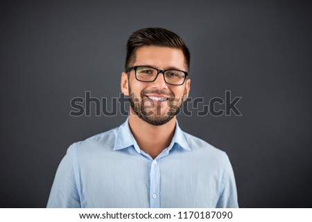 portrait of young bearded hipster guy smiling on gray dark background close up brutal modern man l stock photo © iordani