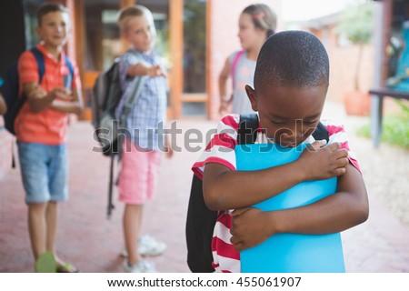 School friends bullying a sad girl in school corridor at school Stock photo © wavebreak_media