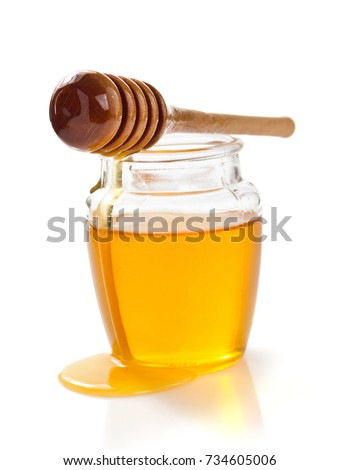 A puddle of honey on the table with glass pot with natural organic dessert on a gray concrete table. Stock photo © artjazz