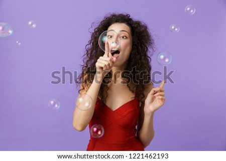 Image of delighted woman 20s wearing red dress laughing, standin Stock photo © deandrobot