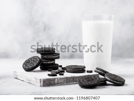 Stock photo: Glass of milk and black sandwich cookies on black stone kitchen table background. Space for text.