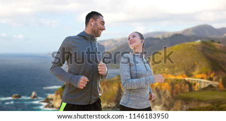 couple with earphones running over big sur Stock photo © dolgachov